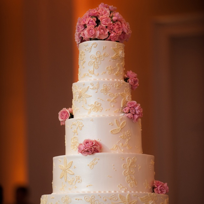 The five-tiered confection was topped with pink spray roses, ivory buttercream frosting and an intricate lace icing detail that matched the overlay on Leeanne's gown.
