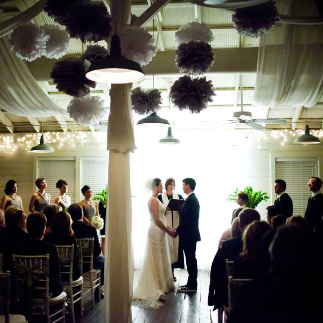 The evening ceremony was decorated with curtains, floral arrangements, uplighting and handmade tissue paper poms.