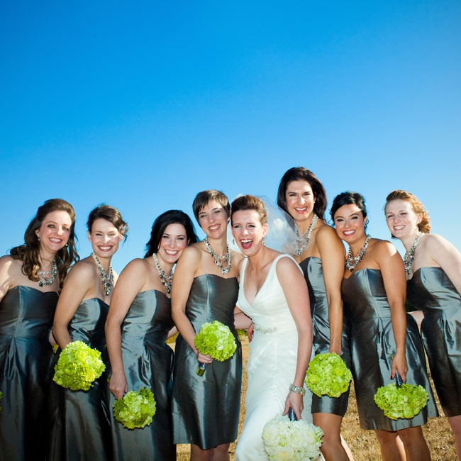 All seven of the bridesmaids wore simple pewter cocktail dresses with sweetheart necklines and statement necklaces that Nicole gifted them.