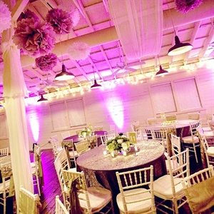 White draping and curtains along with pomanders and glittery linens served as focal points at the reception. Purple uplighting added some drama to the room.