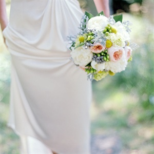 The bouquet was made up of white peonies, green hypericum berry, dusty miller, silver brunia berry, coral garden roses and billy balls wrapped in burlap.