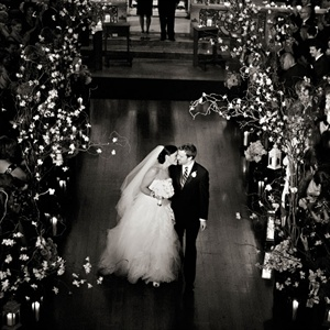 The ceremony aisle was lined with floral branches and candles.