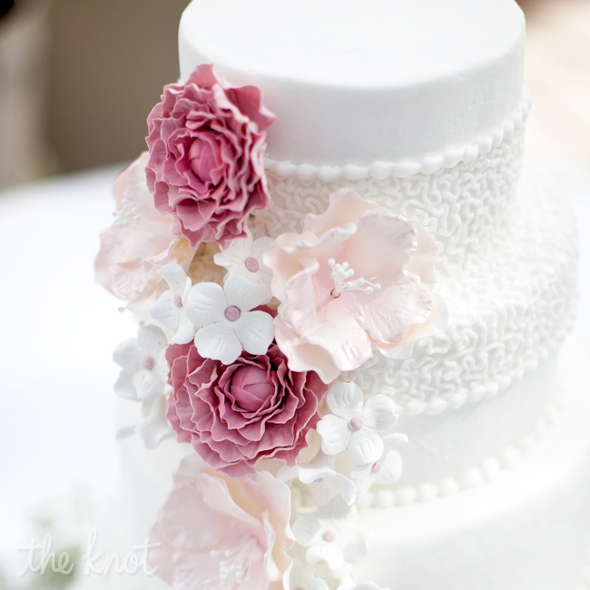 The four-tiered cake was decorated with sugar flowers and lacy piped detailing.