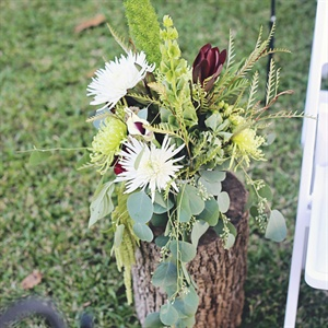 Tree stumps with  rusted pails full of flowers and plants such hydrangeas, seeded eucalyptus, succulents and ferns decorated the ceremony area.
