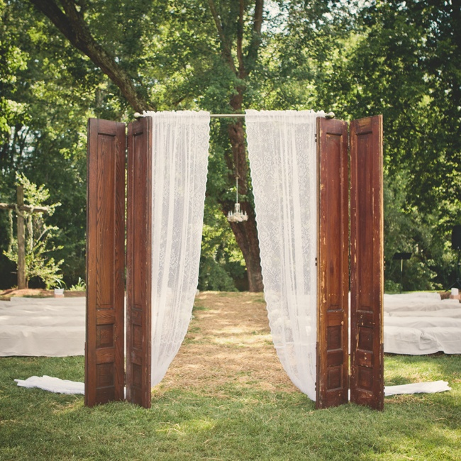 "The ceremony took place at outside, by a creek that runs through the church property.  Elisha and David placed the found antique shutters at the end of the aisle and used lace curtains for the ""grand entrance""."