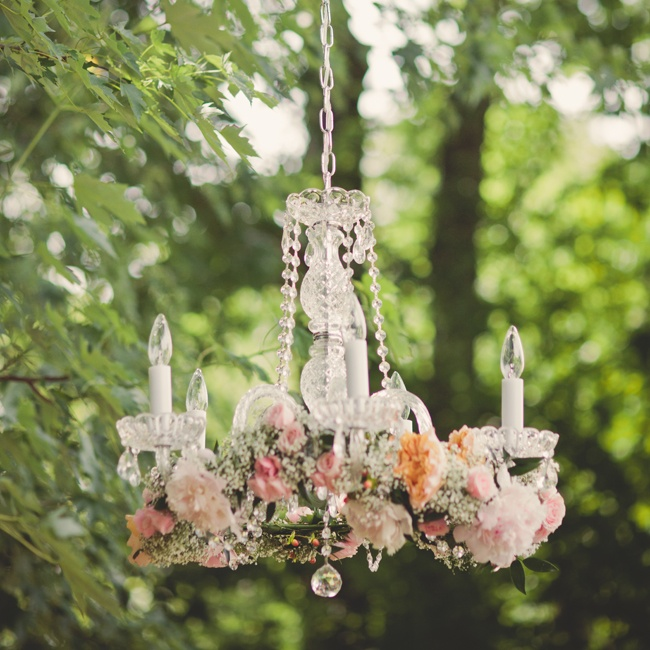 Elisha and David were married under a chandelier hung from a tall tree. The couple's florist made a beautiful garland of Sarah Bernhardt peonie, Juliet garden roses, Pink Majolika spray roses, sahara roses, Peach hypericum berries and million star gypsum to place around the chandelier