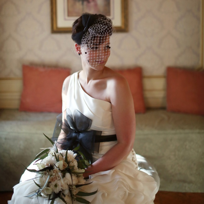 Amber wore a dramatic one-shouldered Vera Wang gown; she added a bold black sash for a unique, personalized touch. To finish it off, she wore a birdcage veil that she actually made.