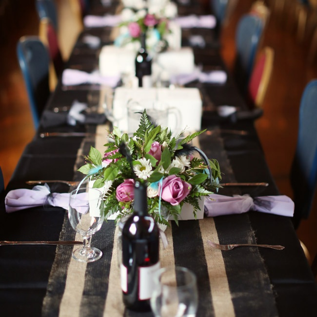 Roses, daisies and various greens were displayed in white milk glass containers. Black-painted burlap runners decorated the tables along with black linens.