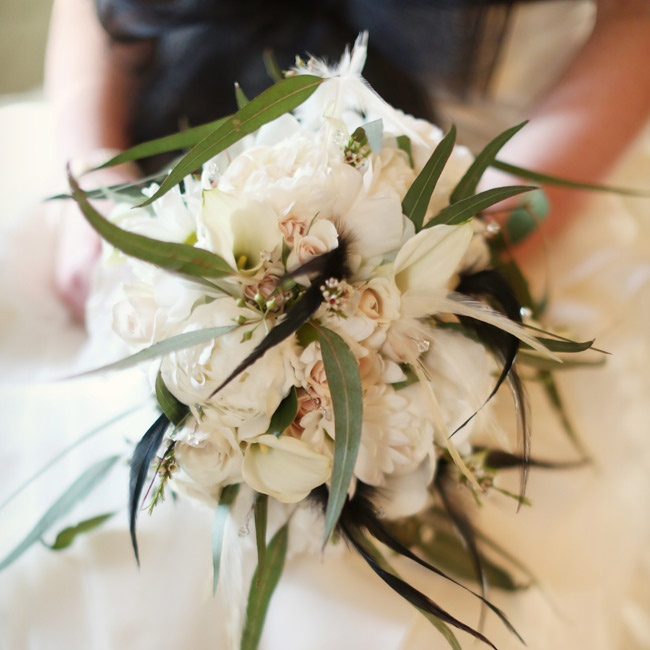 Amber carried a bouquet with white peonies, mini cala lilies, white wax flower, seeded eucalyptus, cream spray roses, white daisies and black and cream feathers.