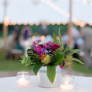 The tables had flowers in galvanized silver French pails and the high top tables had the small galvanized buckets of flowers that were used in the ceremony.  The centerpieces featured light purple, magenta, plum and touch of orange accented with greens.  The flowers were very natural looking, with a mix of stock, gomphrena, hypericum berries, alliu ...