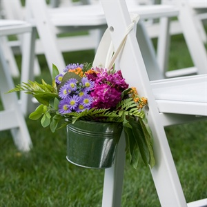 Amanda and Craig wanted simple decor because the inn and grounds had a natural beauty. The couple hung small buckets with flowers hanging from the chairs to decorate the aisle.