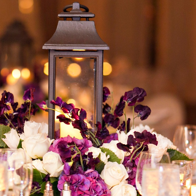 Iron lanterns and a pewter birdcage decorated the antique space which was also sprinkled with purple and white flowers.
