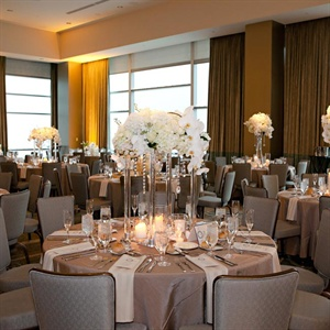 Lush white arrangements of hydrangeas and orchids topped tall glass vases. Draped crystals finished the luxe modern look.