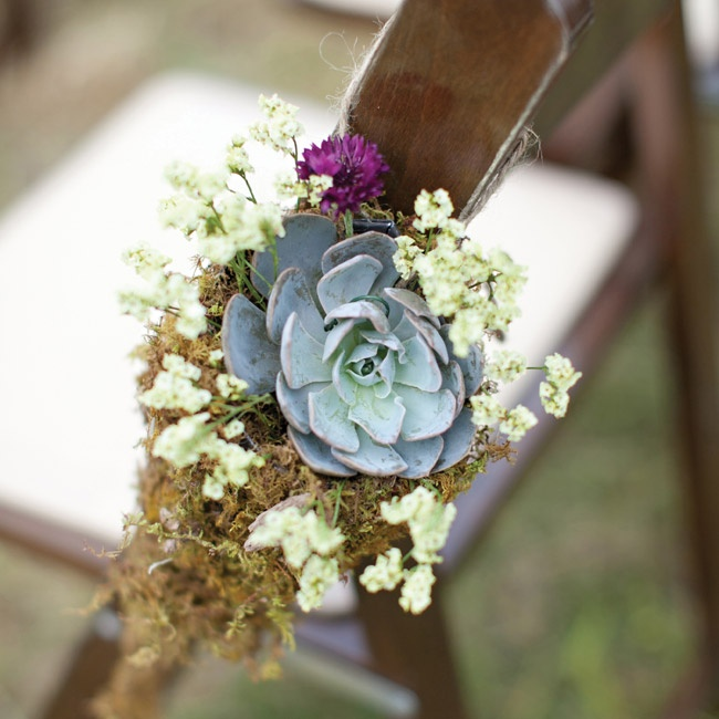 Earthy bunches of moss and succulents embellished the chairs along the aisle.