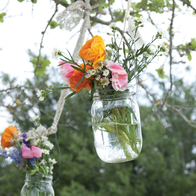 Mason jars filled with loose flowers hung from trees surrounding the lounge seating area.