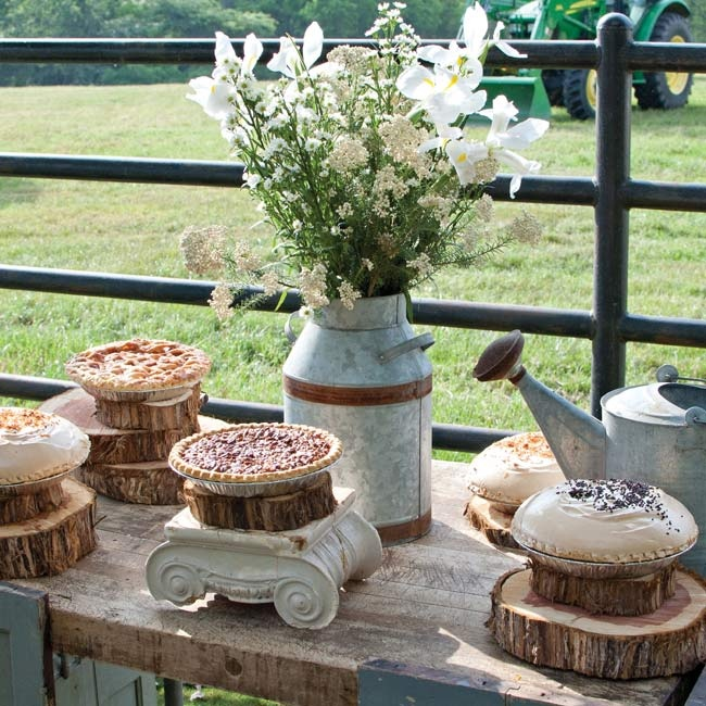 An assortment of tarts and pies rested on charming pedestals made from stacked logs.