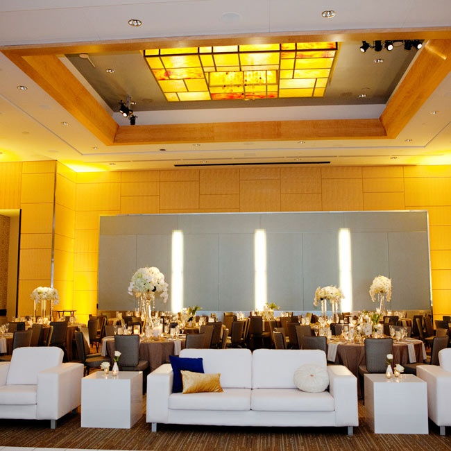 Amber lighting and chic white couches set a modern yet romantic mood at the couple's lounge in the reception.