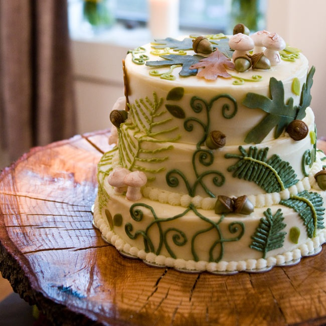 The couple's three-tiered buttercream frosted cake was topped with meringue mushrooms and marzipan acorns and leaves. A friend of theirs made a rustic cake stand from a tree stump.