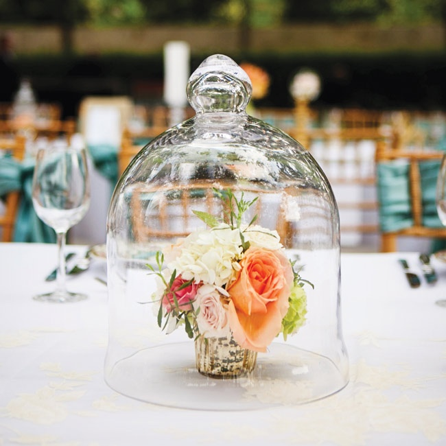 Petite floral arrangements covered with bell jars made for inventive additions to the banquet table.