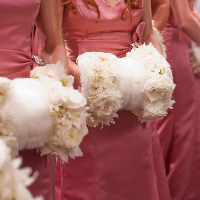 For a unique and wintery twist, the bridesmaids carried fur muffs trimmed with white flowers.