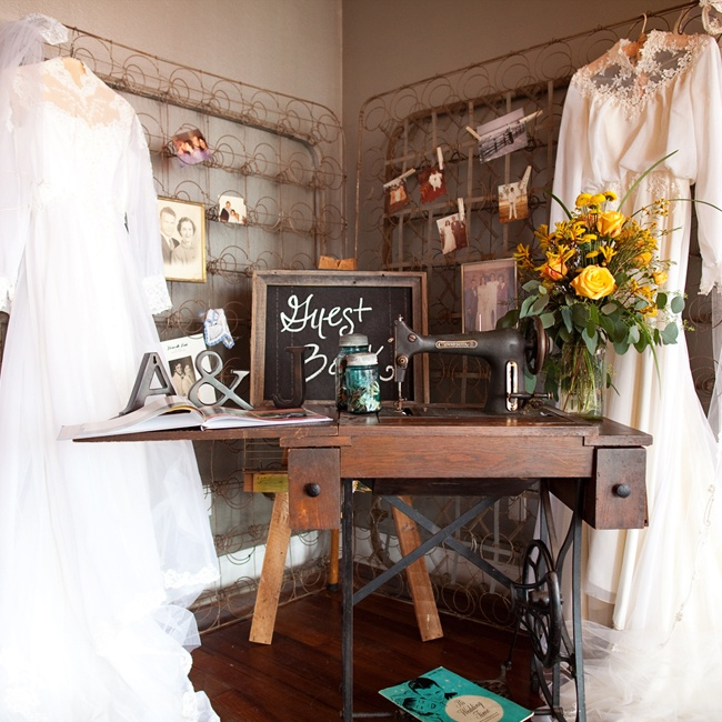 The guest book area was decorated with the wedding dresses worn by the mother of the bride and the mother of the groom. The table had photos of the grandparents and the decorations came from family members.