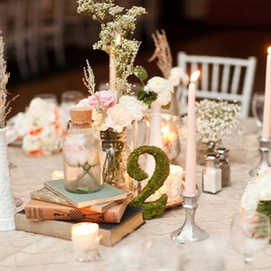 Collected bottles, jars and vintage books decorated the tables along with candles, moss table numbers and soft pastel florals.