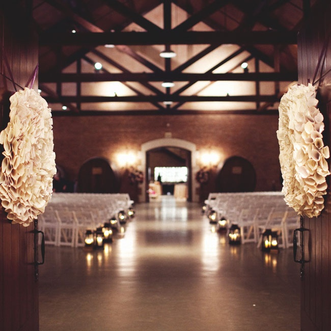 Wooden doors adorned with book-page wreaths opened to reveal a romantic, candlelit room.