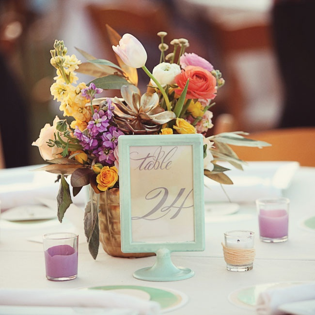All of the wedding colors were represented in the flowers, table numbers and votive candles, creating the watercolor-inspired look the couple wanted.