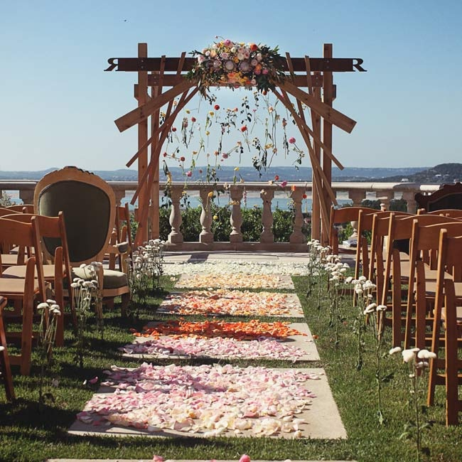 Ombré flower petals lined the aisle at the waterfront ceremony. Vintage chairs mixed in with the folding chairs added character.