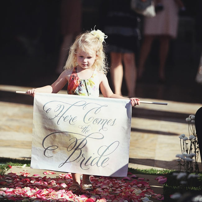 "One of the flower girls carried a ""Here Comes the Bride"" canvas banner designed by Austin."