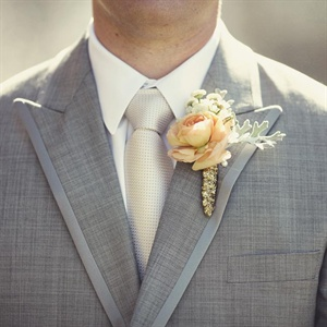 Steven wore ranunculus and dusty miller wrapped in gold ribbon on his suit's lapel.
