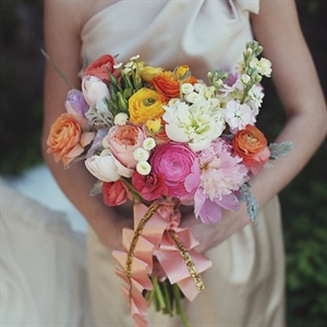The bridesmaids carried soft spring flowers, like peonies, tulips, ranunculus and roses, tied with ruffled pink ribbon.