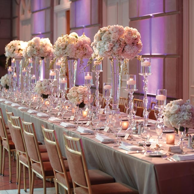 A mix of glass candlesticks and vases topped with lush white flower arrangements had a clean yet glam look.