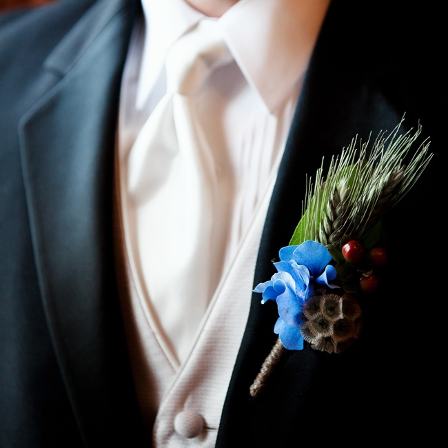 The men's boutonnieres carried through the wheat and grasses theme. The grooms boutonnier had blue hydrangea with chocolate hyericum berries and the grooms.