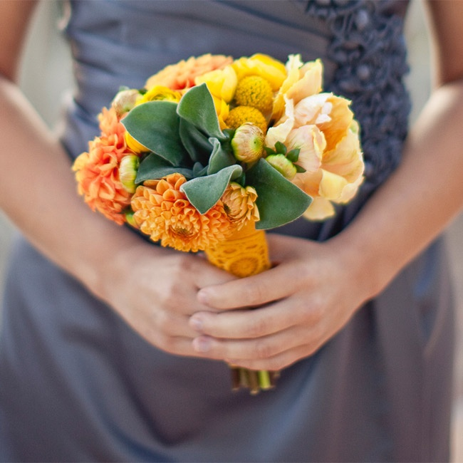 The bridesmaids held orange and yellow bunches of billy balls, dahlias and greens.