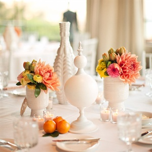 Modern white ceramic vases were displayed on the tables; some were filled with pink, orange and yellow blooms.