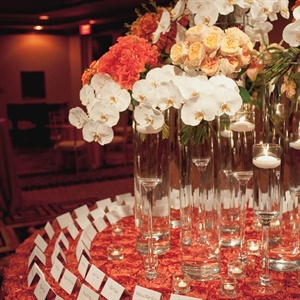 Orchids and roses seemed to spill out of tall glass vases, turning the escort card table into a stunning décor element.