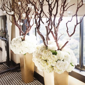 Two arrangements of branches, hydrangeas and hanging candles stood behind the cake table.