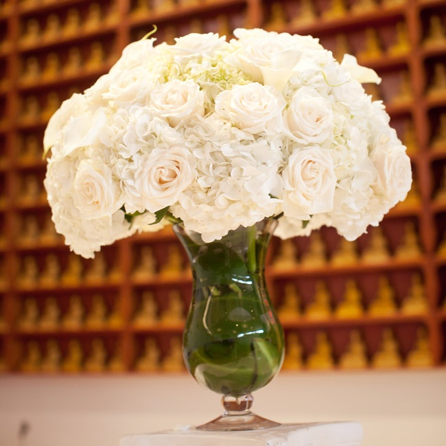 Lush white arrangements of roses, calla lilies and hydrangeas flanked the temple's stage.