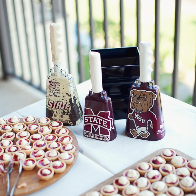 The dessert table of mini strawberry cakes made from a family recipe was decorated with the traditional and infamous Mississippi State University cowbells.