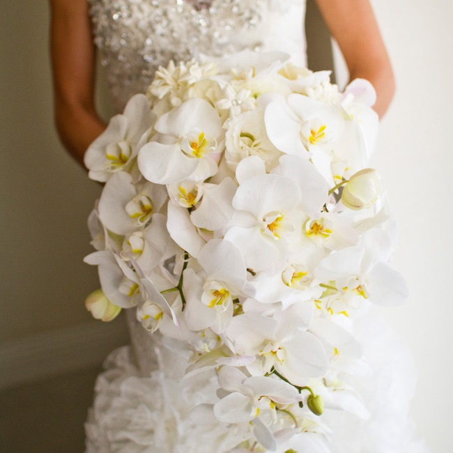 Lily carried an all-white cascading bouquet of phalaenopsis orchids, cattleya orchids, calla lilies and gardenias decorated with rhinestones.