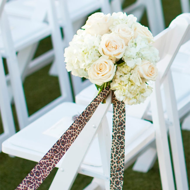 Bunches of cream roses and hydrangeas decorated the ceremony aisle chairs along with leopard-print ribbon.