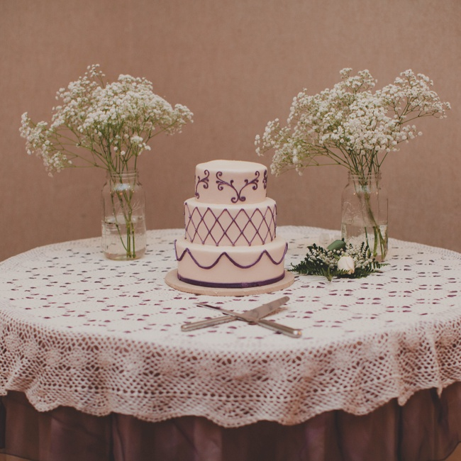 The Bride and Groom chose a three tier chocolate cake with ivory buttercream frosting and different designs on each layer. Lace and two jars of baby's breath gave the cake table a rustic appeal.