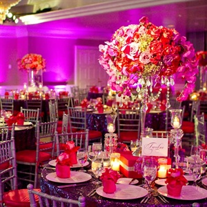 Tall candelabras were topped with hot pink and purple roses and  orchids -- crystals were added for a touch of glam. Candles and smaller arrangements added romance to the evening.