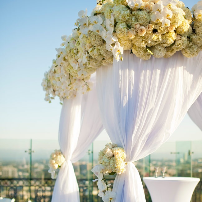 The couple wed beneath a white-draped huppah with white orchids, roses and hydrangeas finishing it off.