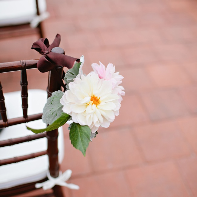 Mason jars tied to ceremony chairs were filled with white and pink dahlias.