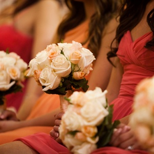 The girls carried small bunches of cream and pale peach roses to complement their coral dresses.