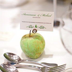 The couple found cement apple and pear paperweights. They placed one at each place setting and put thank you notes tucked into the wire stems.