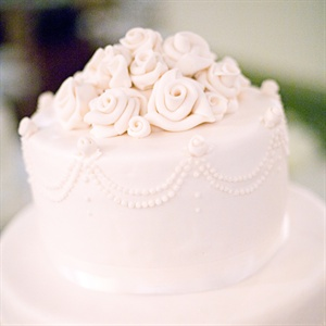 The couple&#39;s cake was draped in fondant and topped with fondant roses and ivory satin ribbon.