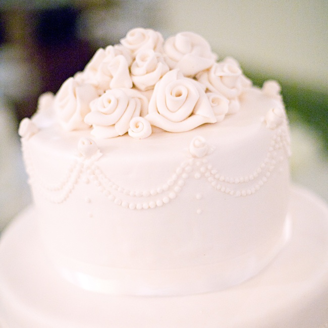 The couple's cake was draped in fondant and topped with fondant roses and ivory satin ribbon.